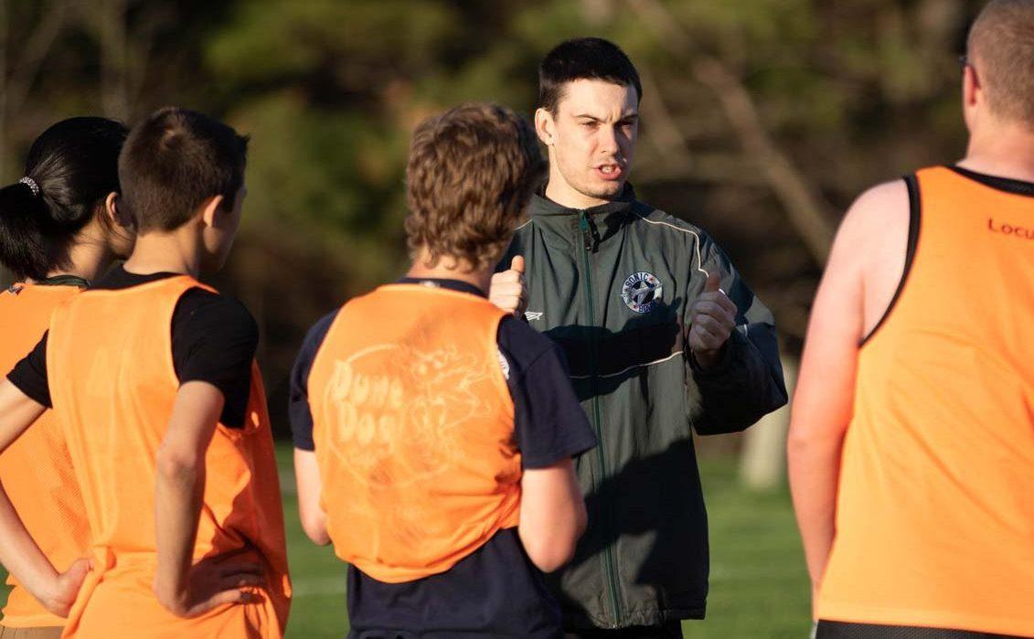 A coach describing a play to a group of youths