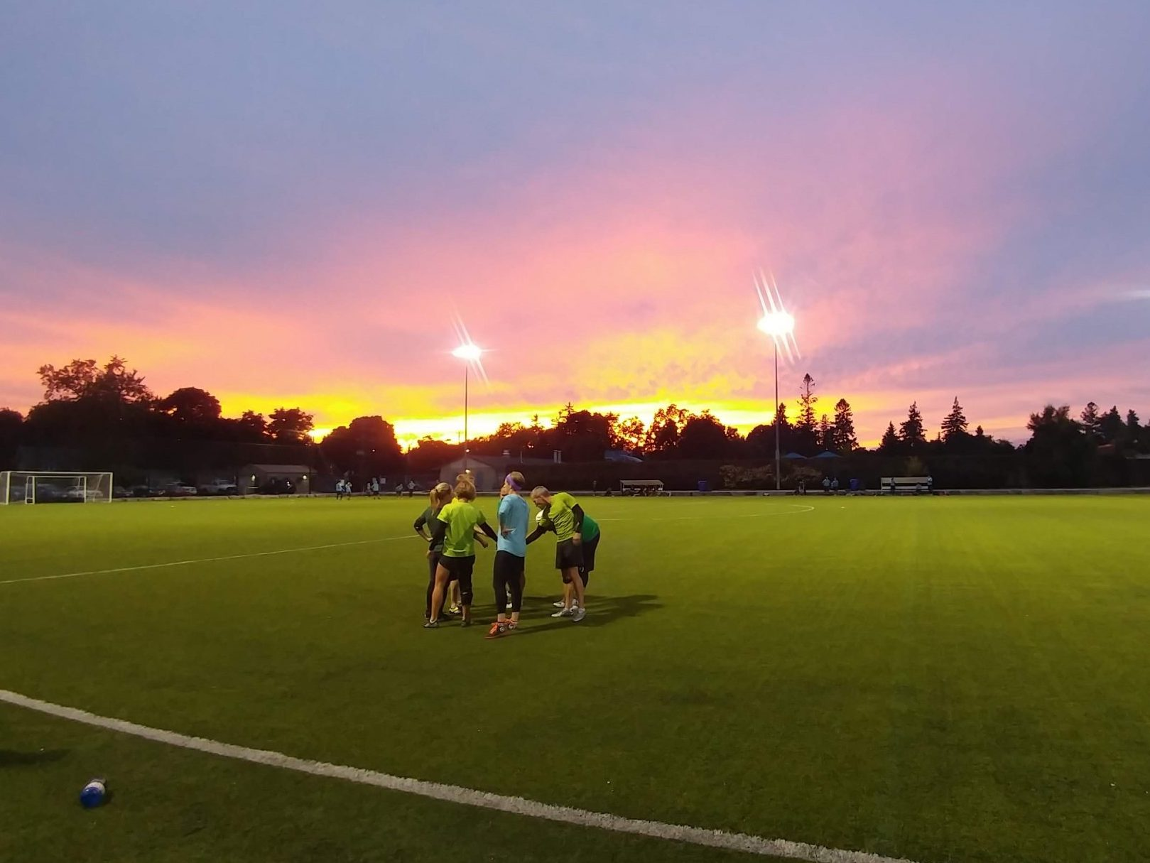 A team circles for a huddle on a turf field at sunset